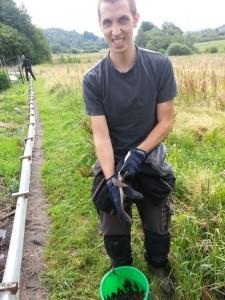 Johannes plockar sniglar längs staketets utsida